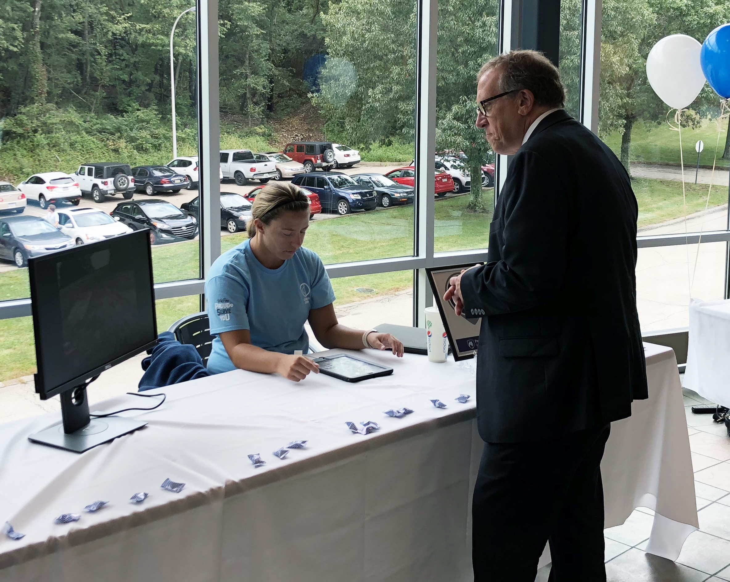 Student showing Vice President of Information Technology Michael Kubit how Physical plant is using iPad.