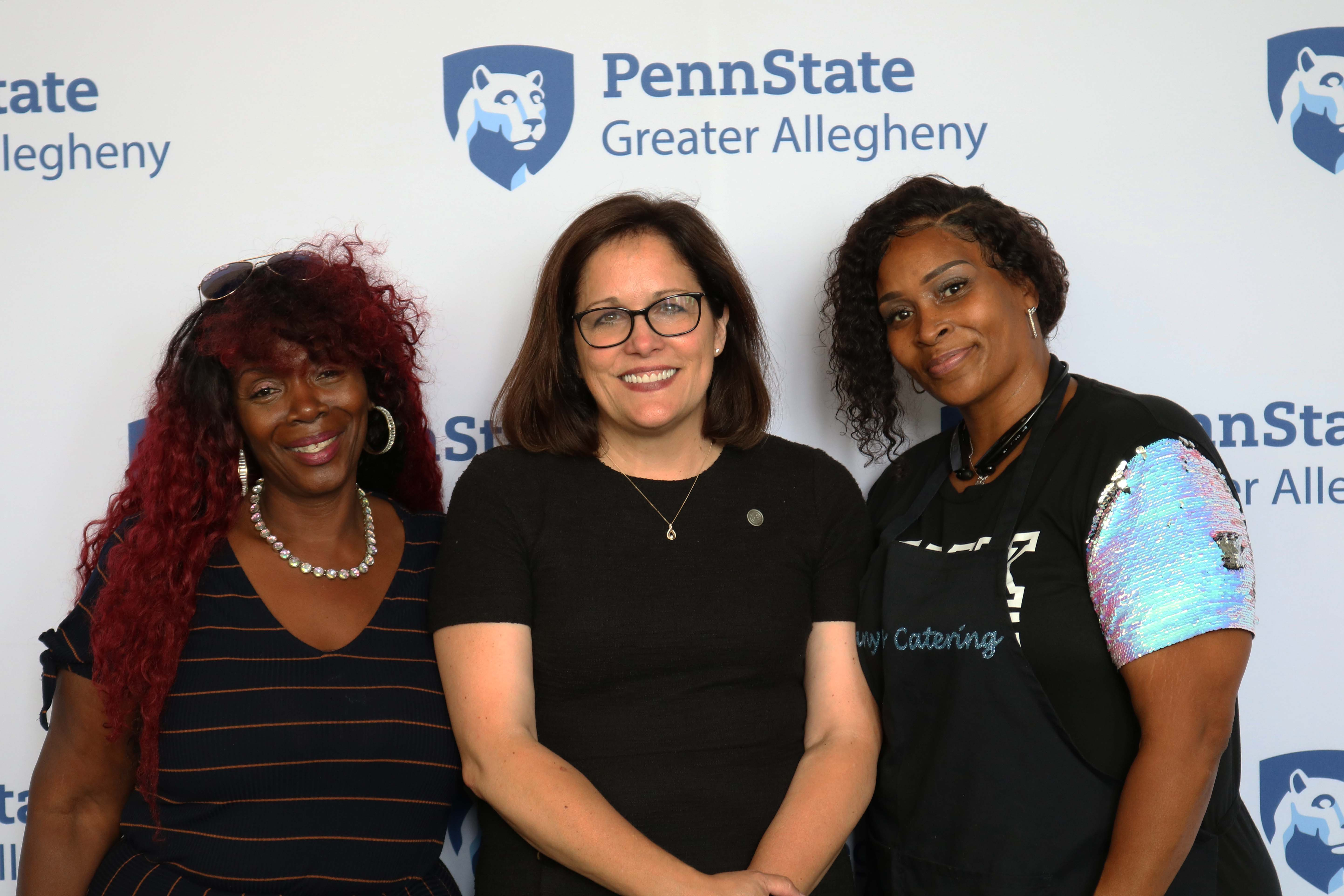3 women smiling standing in front of Penn State Greater Allegheny Logo