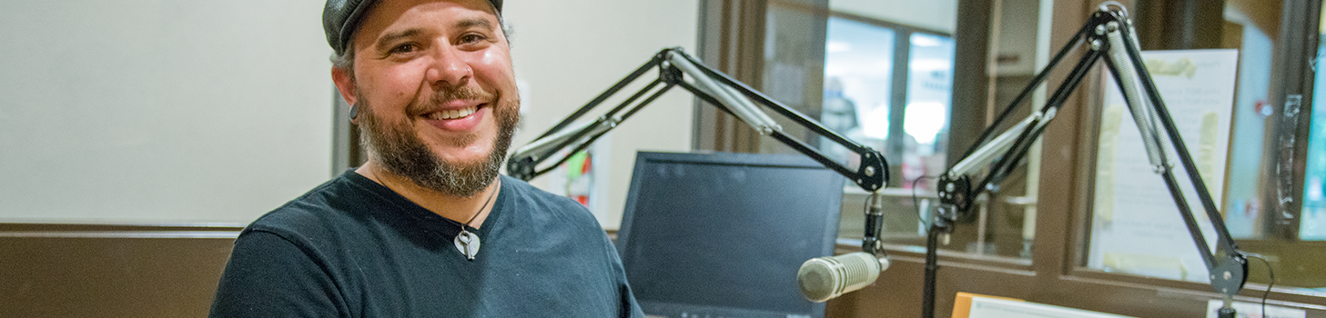 Dr. Zack Furness in the campus radio station smiling
