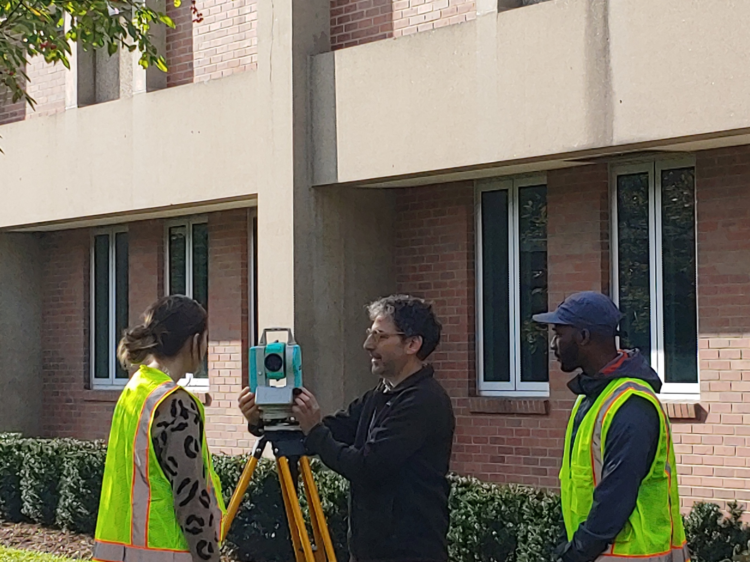 two students and a professor setting up a surveying camera in front of building