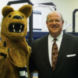 Regis W Becker standing next to Nittany Lion mascot