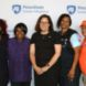 a group of women smiling, standing in front of Penn State Greater Allegheny Mark
