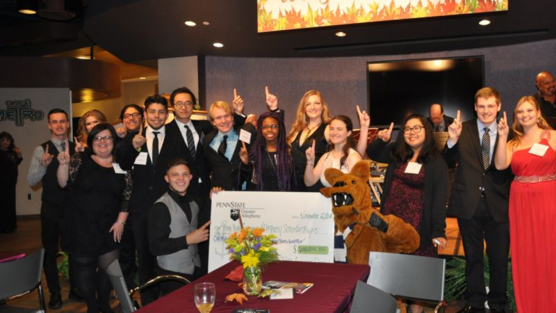students dressed up holding big check