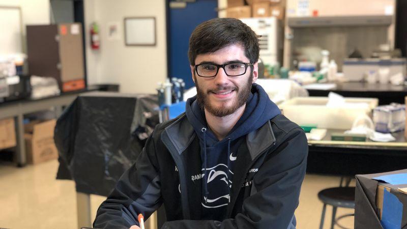 Wyatt Thomas sitting in a research lab