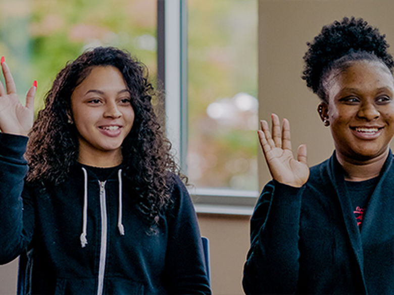 two students raising their hands.