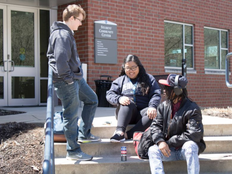 Three Students sitting on the stairs outside of the Student Community Center