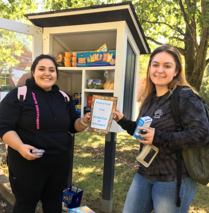 Two students standing in front of the little food pantry