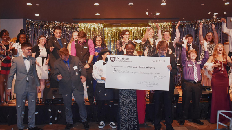 Students reveal donation total at 2017's All That's Jazz scholarship benefit.
