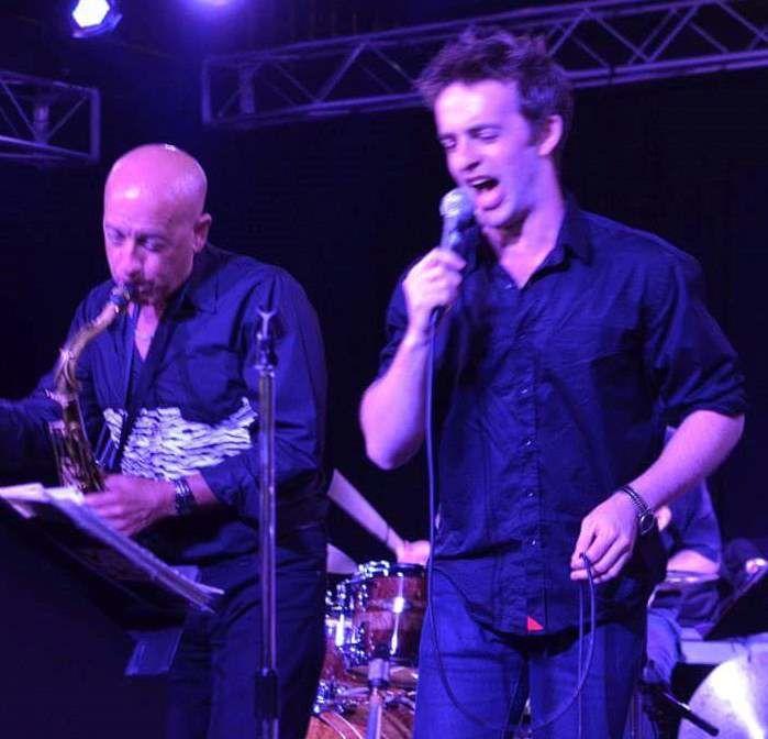 man singing and man playing saxophone