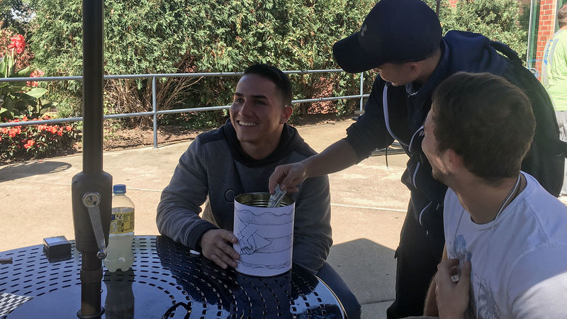 Students Pedro Escobar and Marcos Lopez collect a donation from Dash Phuyel in a can wrapped in a drawing of the Puerto Rican flag outside of Café Metro.