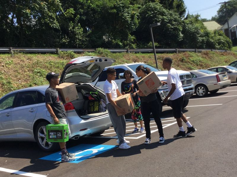 people moving boxes near cars