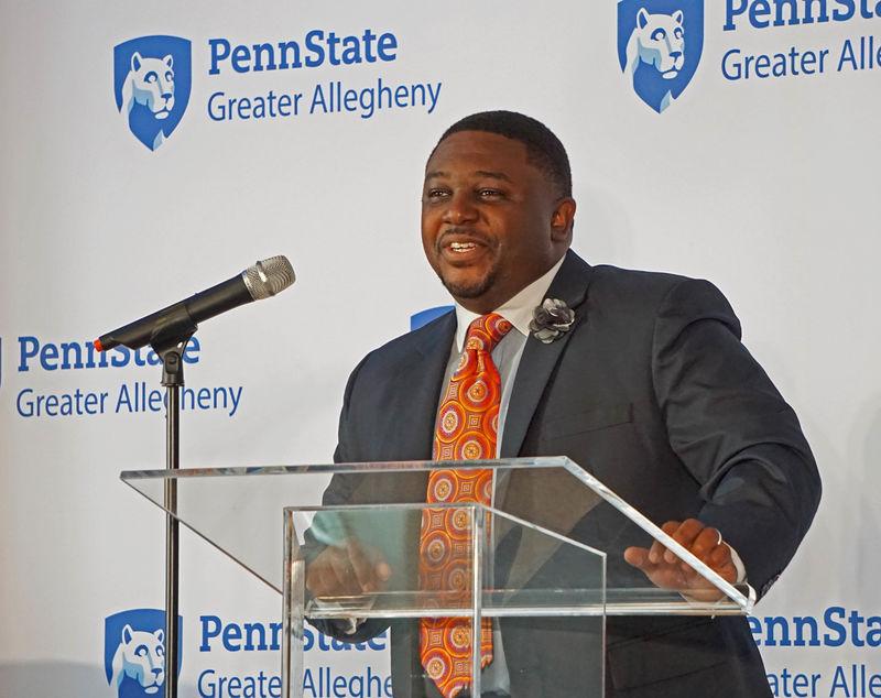 man speaking at podium into microphone