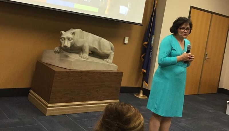 woman speaking in front of lion statue