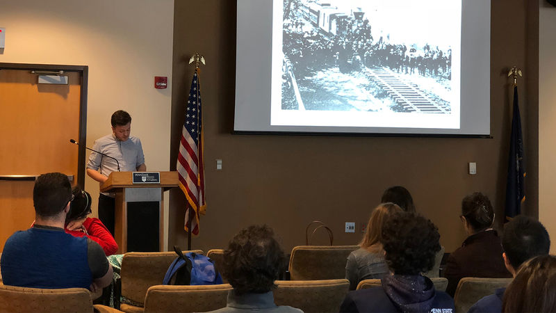 Presenter discussing current slide of old Pittsburgh to students