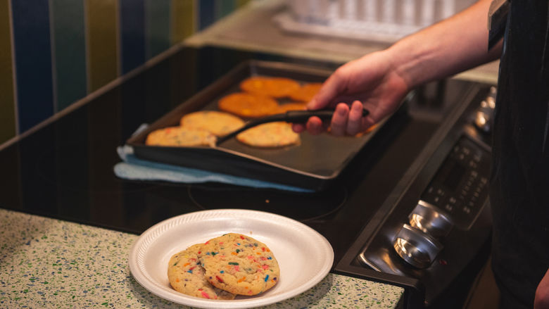 Student removing cookies from a baking sheet