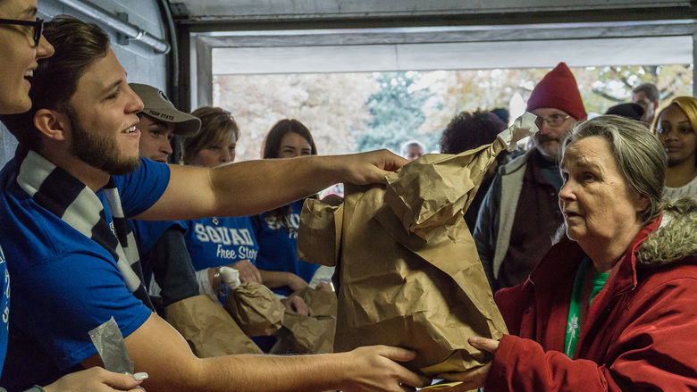 Students bag meals for a community member.