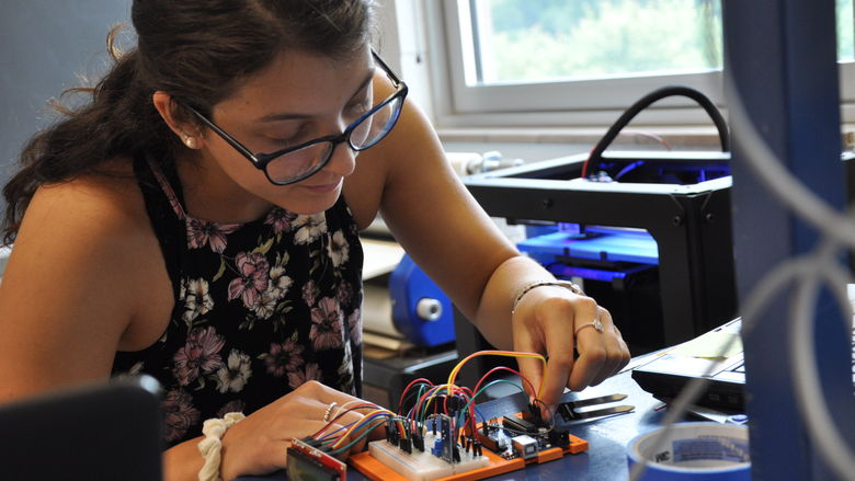 female student using 3-D printer