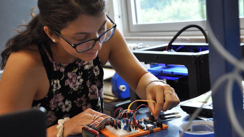 female student using 3-D printer