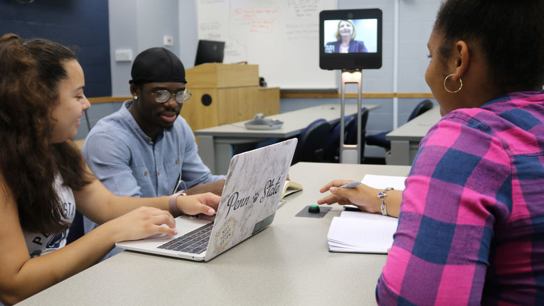Three students learning from a professor on a lcd monitor attached to a robot.