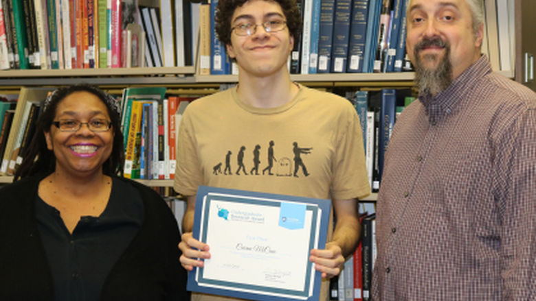 Three people standing in front of a bookshelf smiling. The person in the middle is holding an award.