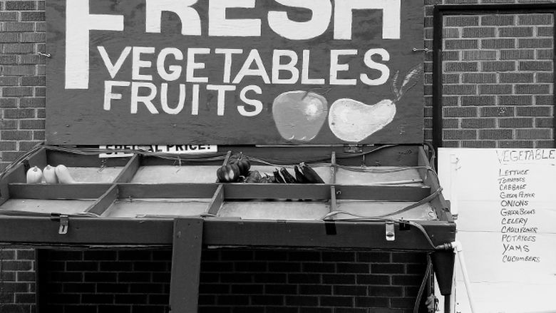 Produce stand with a sign that reads Fresh Vegetables Fruits