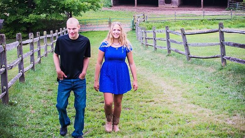 woman and man walking in field