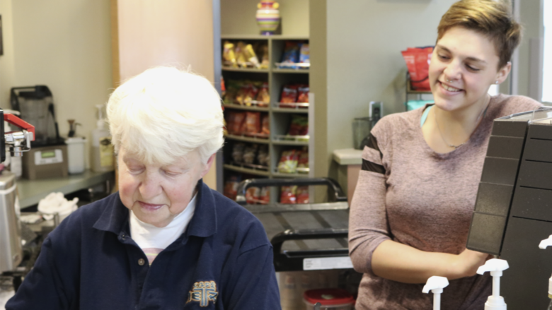 Student smiles as campus favorite barista prepares coffee